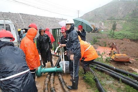图一为中州铝业保障中心员工冒雨在现场搬运潜水泵设备,以应对未来几天更加严峻的汛情。