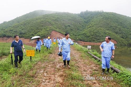 第三张:万基控股集团董事长李跃民(左二)检查万基发电公司山口灰库堤坝加固情况