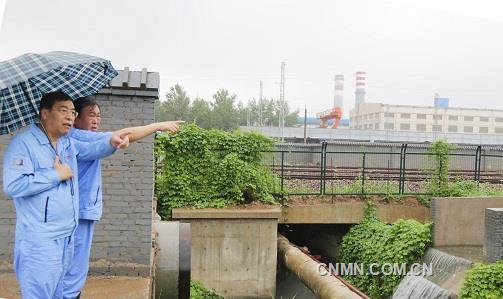 第二张:万基控股集团董事长李跃民(左前)检查万基金属钠公司泄洪渠洪水流向